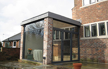 Modern extension to Listed building using aluminium, zinc and glass